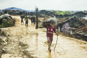 Drenge og mænd henter pinde og kviste fra dalen, som skal bruges til at bygge hytter med.